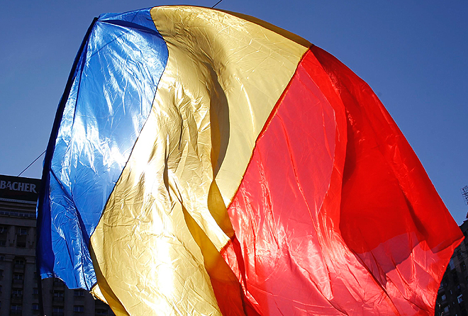 Man waves Romanian national flag during a march in downtown Bucharest